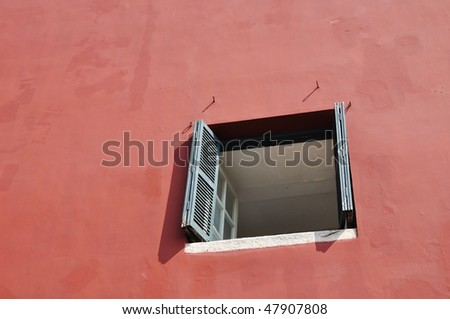 a red wall around a blue window - stock photo