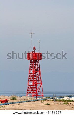 A red warning beacon on the edge of a port