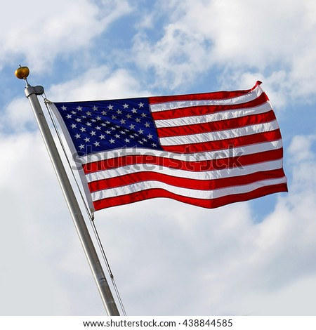 A red, white and blue American Flag is blowing in the wind in front of a cloudy blue sky.