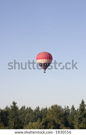 A red, white and blue hot air balloon floats above the trees in woodinville, washington - stock photo