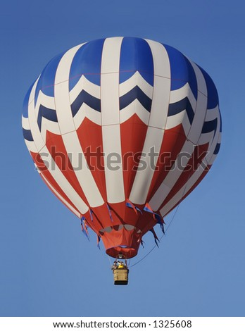A red, white, and blue hot air balloon silently drifts across a clear blue sky.