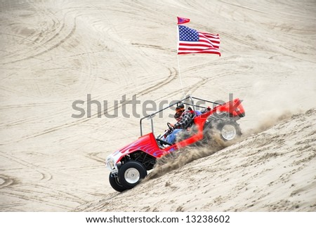 A red white and blue sand buggy with an American flag turning at the top of a steep climb up a sand dune. - stock photo