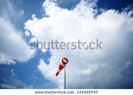 A red wind vane against a blue cloudy sky - stock photo