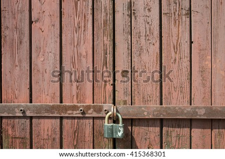 A red wood door closed with a weathered rusty lock  - stock photo