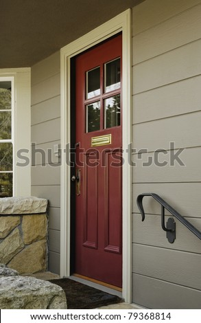 A red wooden front door to a home with four window panes in the top half of it. There is a low stone wall bordering a covered porch. Vertical shot. - stock photo