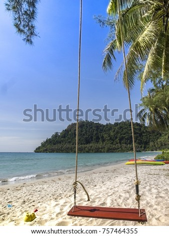 A red, wooden swing hangs from a palm tree on a beach on the tropical island of Ko Kut, east Thailand