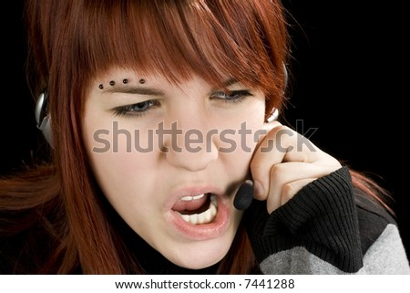 A redhead girl swearing on the microphone talking to a customer or being impolite and stressed. Studio shot. - stock photo
