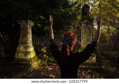 A redhead woman or witch is raising her arms and performing a ritual by a grave - stock photo
