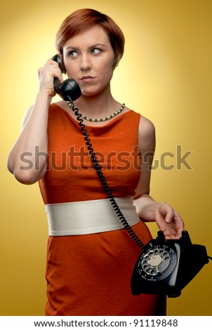 A redheaded woman in a 1960's vintage orange dress holds a 1960's vintage telephone. Photographed in front of a yellow backdrop with studio lighting. - stock photo
