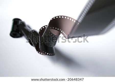 A reel of film rolling downwards, twisting the film along the way. - stock photo