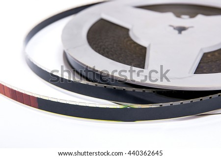 A reel of motion picture film on a white background. Close up view of old film strip isolated on white background. - stock photo