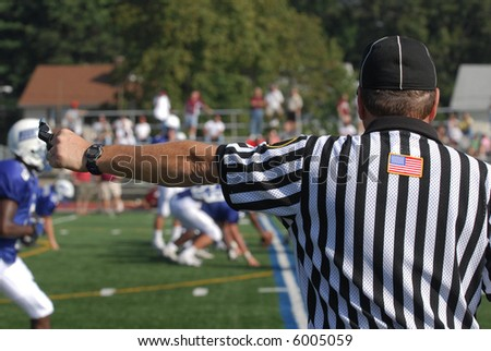 A referee at an North American Football game.  He has his arm extended his whistle and stop watch are visible.  There is an active game with players and spectators in the blurred background - stock photo