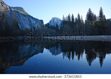 a reflection of half dome of yosemite over merced river - stock photo
