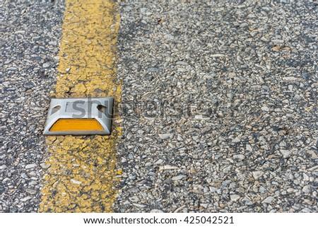 A reflector on the asphalt road. - stock photo