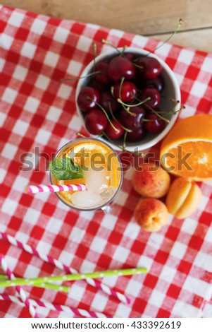 A refreshing summer drink with orange and mint in a glass beaker. Drink and fruit on a vintage tablecloth. Top view. - stock photo