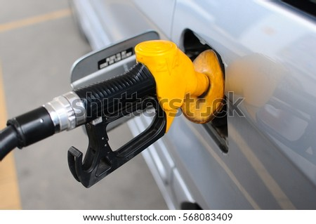 A  Refueling Car's Tank by Petrol Pump Nozzle