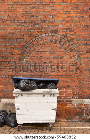 A refuse disposal bin overflowing with black plastic bags containing the discarded rubbish of modern society. - stock photo