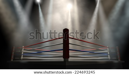 A regular boxing ring surrounded by ropes spotlit by various lights on an isolated dark background - stock photo