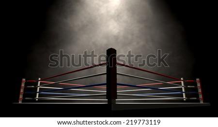 A regular boxing ring surrounded by ropes spotlit in the middle on an isolated dark background - stock photo