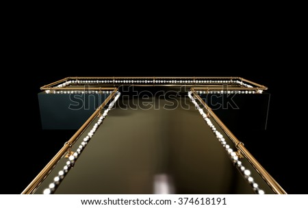 A regular empty stripper stage with a bronze railing and a strip of lights on a dark background - stock photo