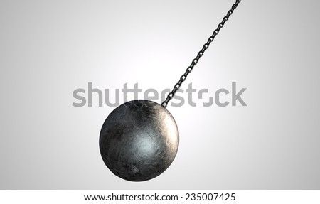 A regular metal wrecking ball attached to a chain on an isolated white background - stock photo