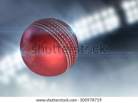 A regular red cricket ball flying through the air on an indoor stadium background during the night - stock photo