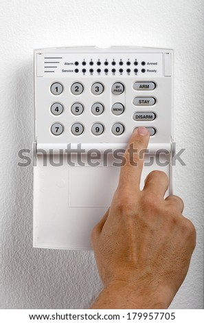 A regular security systems keypad with buttons being pressed by a mans hand on a white textured wall