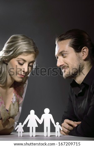 A relationship issue is being discussed by a couple at an intimate meeting. The man gazes intently at the woman who casts her gaze down to a paper cut out of a man, woman and two children. - stock photo