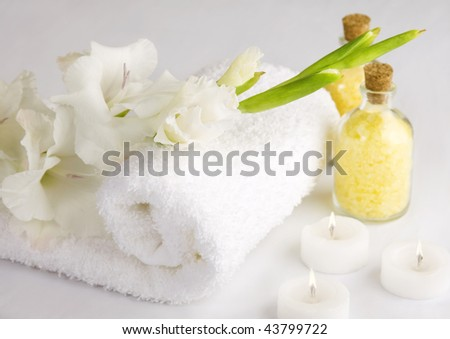 A relax spa scene with towel, bath salts, candles and flowers. - stock photo