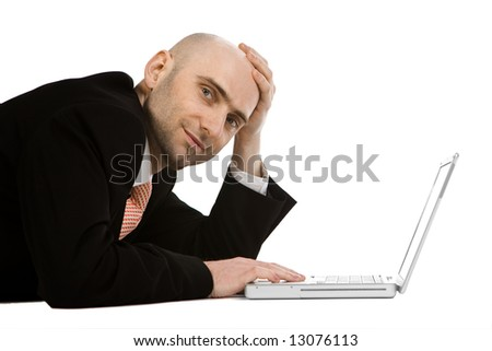 A relaxed businessman lying on the floor with his laptop computer, isolated on a white background
