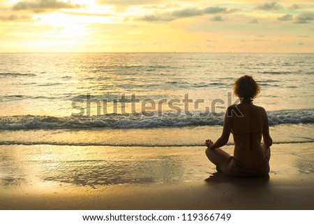 A relaxed sexy young girl wearing a bikini sitting on a deserted tropical beach at sunset. - stock photo