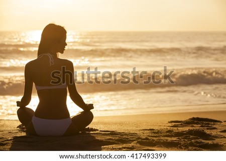 A relaxed sexy young woman or girl wearing a bikini sitting on a deserted tropical beach at sunset or sunrise - stock photo