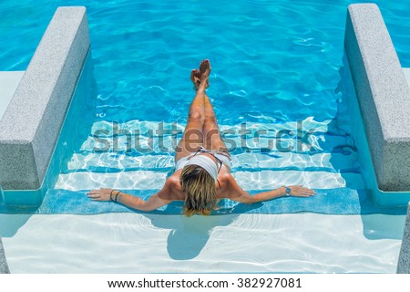 A  relaxed woman in the pool - stock photo