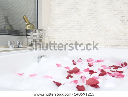 A relaxing bath with rose petals - stock photo