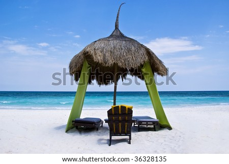 A relaxing beach palapa, complete with colorful fabric walls, deck and wooden beach chairs. A dream vacation setting, like paradise. - stock photo