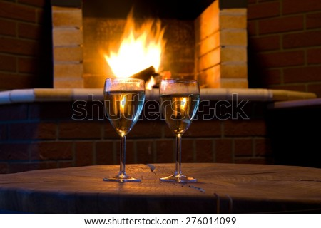 A relaxing evening - glass of wine fireside - stock photo