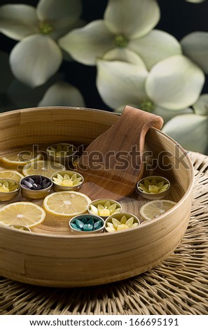 A relaxing spa water with lemons and candles - stock photo