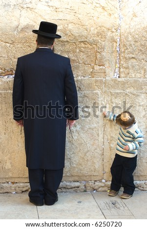 A religious orthodox Jew prays at the Western wall. A little boy inserts into a crack of The Western Wall a scrap of a paper with the request to The God. Jerusalem, Israel. - stock photo
