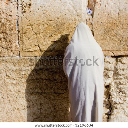 A religious orthodox Jew wearing a prayer shawl draped prays at the Wailing Wall. Jerusalem, Israel. - stock photo