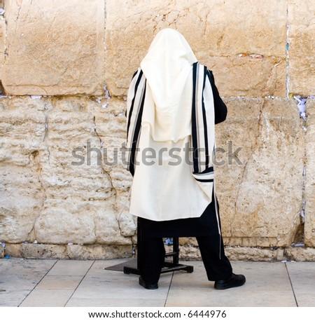 A religious orthodox Jew wearing a prayer shawl draped prays at the Wailing Wall. Jerusalem, Israel. - stock photo
