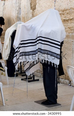 A religious orthodox Jew wearing a prayer shawl draped prays at the Western wall. Jerusalem, Israel. - stock photo