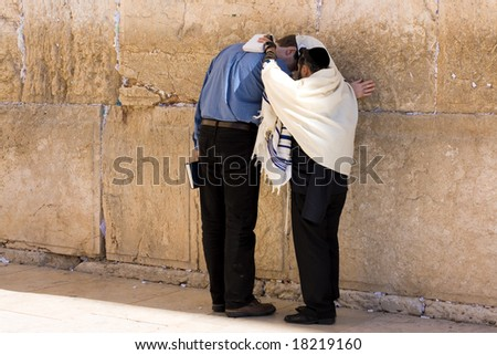 A religious orthodox Jews wearing a prayer shawls draped prays at the Wailing Wall. Jerusalem, Israel. - stock photo