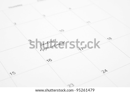 A reminder is wrote on a calendar to go to the dentist appointment. - stock photo