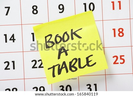 A reminder to book a table or make a reservation for dinner on a yellow paper sticky note stuck to a wall calendar background - stock photo