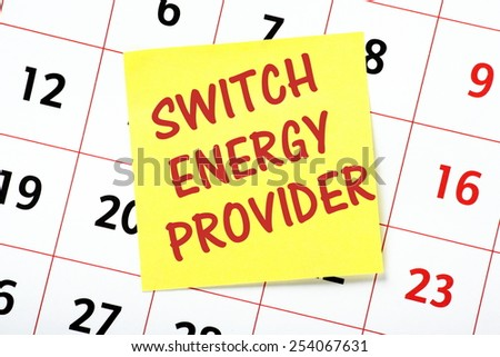 A reminder to Switch Energy Provider written in red ink on a yellow sticky note and pasted to a wall calendar - stock photo