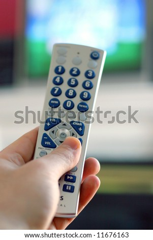 A remote control in action - shallow depth of field, with focus on the remote. - stock photo