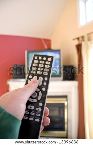 A remote control in hand - shallow depth of field with focus on the remote. - stock photo