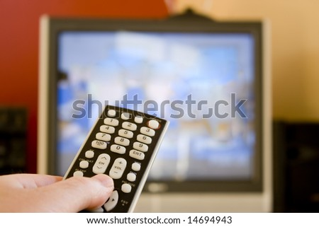 A remote control in hand.  Shallow depth of field, with focus on the remote. - stock photo