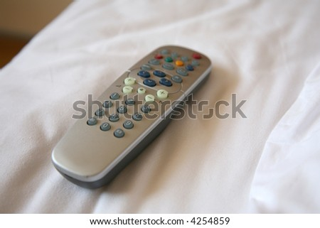 A remote control on a bed - stock photo