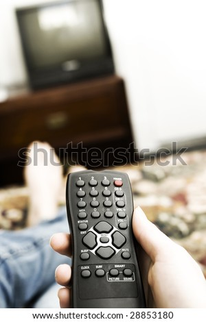 A remote controller sits on the lap of a person laying on a hotel bed. - stock photo